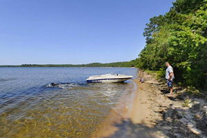 Photo of a boat anchored in the shallow water on a hot summer day.