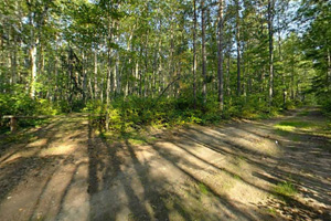 Photo of part of the park's eighteen miles of trails that wind through heavily wooded hills and around pothole lakes.