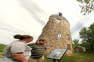 Photo of park visitors inspecting the rebuilt historic granary.