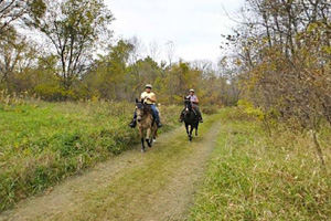 Photo of a pair of horseback riders traveling on the Lawrence Unit trail.
