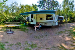 Photo of a woman reading outside her camper at the Moose Lake State Park campground.