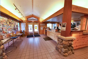 Photo of the entryway inside the Moose Lake State Park visitor center, with a DNR staffer behind the desk.