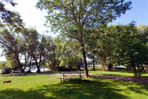 Photo of several picnic tables with the lake in the background.