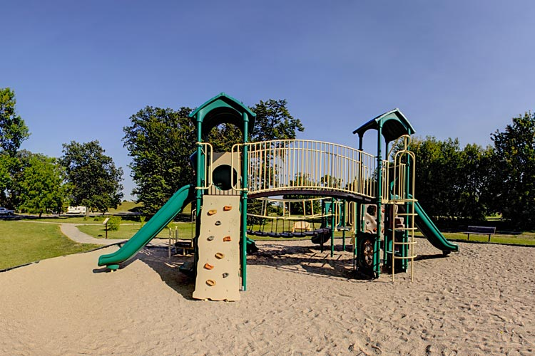 Photo of Sherlock Park Campground where children can enjoy slides, swings, and other play equipment .