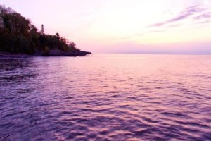 Photo of a rosy colored sunrise over Lake Superior.
