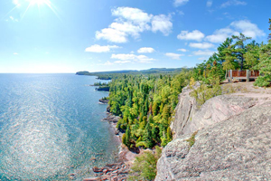 Photo of stunning view down the shoreline traverses sea caves, a sea stack, the mouth of the Baptism River, and Palisade Head.