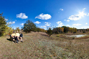 Photo of a couple resting on a bench near the Rolling Hills Trail.