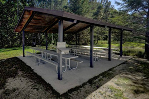 Photo of a shaded picnic shelter, just off the gravel parking area.