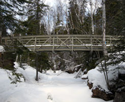 Photo of a bridge spanning the ice-covered river at the Kodonce River Wayside in winter.