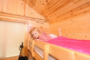 Photo of a child on the top bunk of a camper cabin within the park.