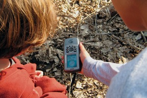 Photo of park visitors using a device to discover a geocache.
