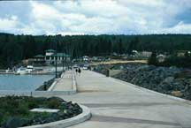 A view of the walkway along the breakwater, looking back at the Silver Bay Marina office building and adjacent parking lot.