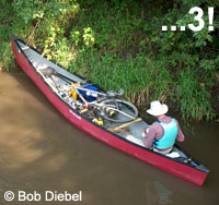 Photo of a paddler in his canoe, with his bicycle packed into the center of the canoe