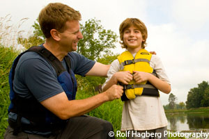 Dad helping son with his lifejacket