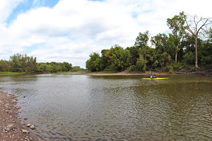 Photo a portion of the Minnesota River, near Morton, which is mostly flat water with no rapids or obstacles beyond a fallen tree or two.
