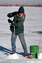 Drilling a hole in the ice with a hand auger
