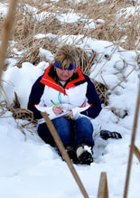 Rockfore teacher training- teacher writting a jounral sitting in the snow.