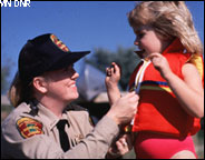 Image of MN DNR Conservation Officer zipping up a life vest on a child.