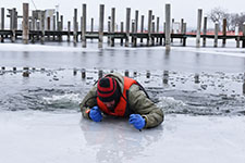 person using ice rescue claws to pull themselves out of lake
