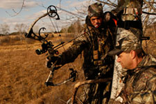 Adult helping teenager hunting deer with a bow.