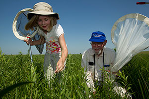 An adult and child with insect nets learn about the prairie ecosystem.