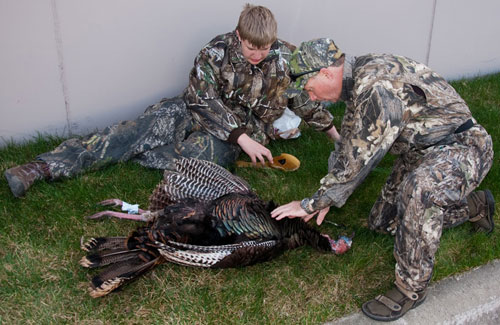 An NWTF outdoor coach explains to a youth outdoor explorer participant how to clean a wild turkey.