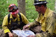 two wildland firefighters looking at map
