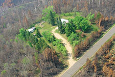 image image of a home sown in green surrounded by burned forest