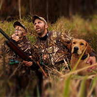 father and son duck hunting in marsh with their dog
