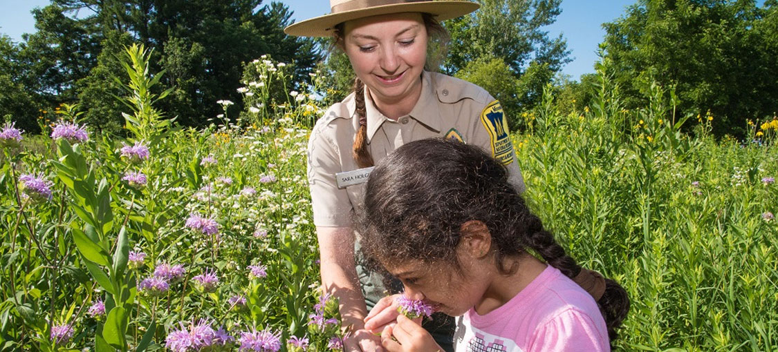 Park naturalist teaching a child about nature