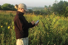 women standing with GPS reporting an invasive species