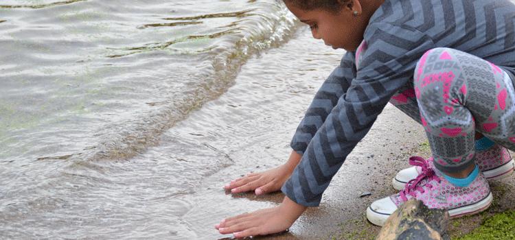 child touching surface of lake