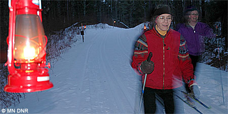 Two cross-country skiers on a lantern-lit trail.