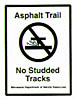 Sign: Asphalt Trail - No Studded Tracks, warning snowmobilers to stay off the trail.