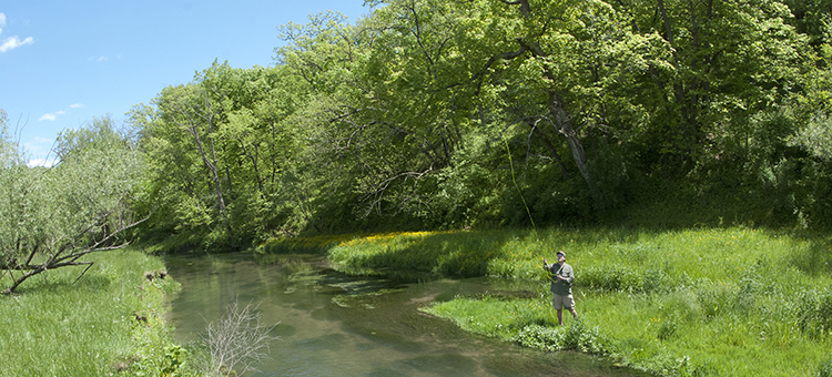 man fly fishing by stream