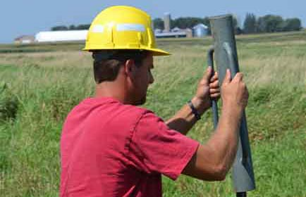 A seasonal worker installs a post for a WMA boundary sign.