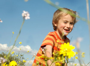child in field of flowers