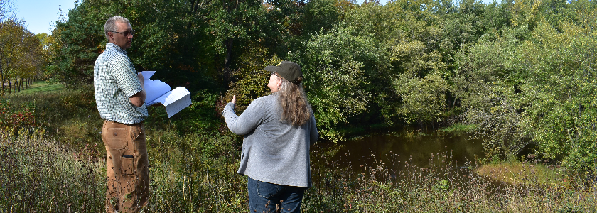 A man and a women standing next to a creek. The man is pointing off in the distance and the women is taking a picture with a camera.