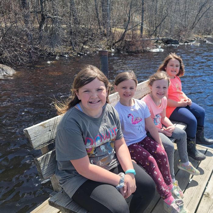 Four young girls on a bench on a lake dock.