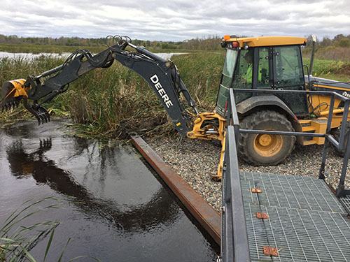 A backhoe moves aquatic plants for maintenance of a wetland control structure.