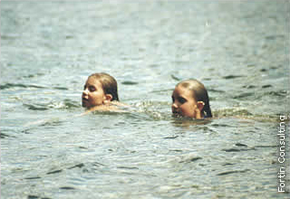 children swimming in a lake