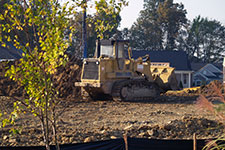 bull dozer with dirt piles and tree in forground.