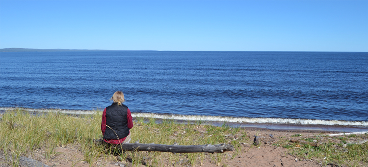 Sitting on beach looking over Lake Superior at Minnesota Point Pine Forest
