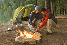 two people kneeing by camping fire with a tent and lake in background