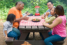 family sitting at picnic table eating
