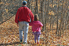 Adult and child hold hands on a leaf-covered trail