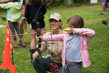 Boy aims his arrow at a target