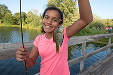 Grinning girl shows off a fish still on the line