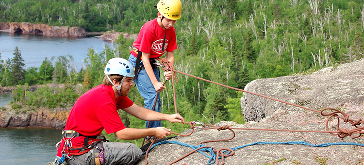 child learning how to rock climb with an instructor