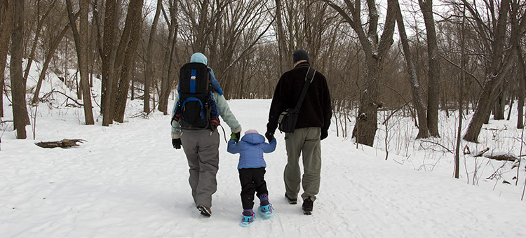 A family hikes in the snow